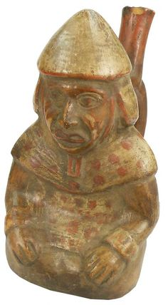 Chimu Culture Pottery :    Red terracotta vessel with a single-handled spout to the back, the body in the shape of a figure wearing a tunic, cape, and conical shaped hat, a red dotted design on the clothing.  1200-1450 AD