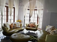 Classy living room with leather finish customized sofa elements and cushions - marble floor and french doors with glass work -lovely curtains from double height space and lovely chandelier - carpet at floor .
