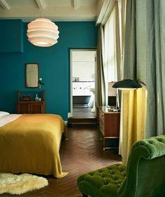 couleur mur bleu petrole, canapé vert, couverture de lit jaune, commode et coiffeuse en bois, parquet en bois, idee deco chambre vintage chic