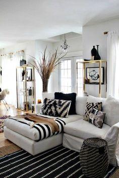 Sala de estar com tapete preto com listras brancas, sofá cinza claro, branco gelo, estantes douradas e pele decorativa. Dicas e Inspirações de Mantas para Sofá