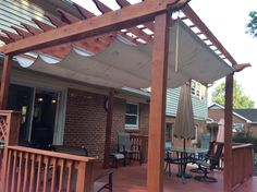 Pergola Shade. Made with a painters tarp from Home Depot, a rubber stamp and craft paint from Hobby Lobby, 2 cans of waterproofing scotch guard, plumbing conduit, wire and carabiners. Total cost about $80 and a day of work.