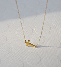 Gold sideways cross necklace - modern celebrity jewelry