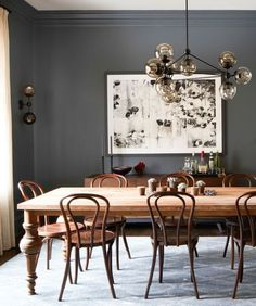rich neutrals in this dining room with a mix of modern lighting and farm table with thonet chairs