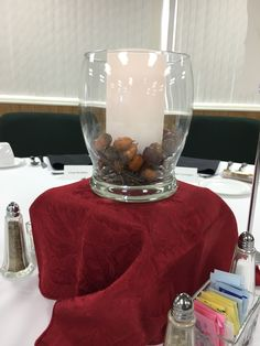 Havard Convocation and President's Luncheon Fall 2016 tablescape- This tablescape used grapevine and acorns in a vase with a soft pillar candle. Sitting a top a wood box covered in gold, burnt orange, and burgundy fabric