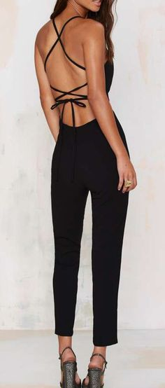 The Raquel Jumpsuit is black and features a sweetheart neck, cross-back design, and enclosed zipper at back. Wear it with a leather moto jac...