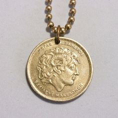 Greece Alexander the Great Coin necklace Pendant charm 100 drachmas Greek coin jewelry.  - This is a genuine Greek coin, circulated in 1994.  - Quantity 1  - Choose a style: chain necklace / Cord necklace / Key chain  - According to your selection, your coin will arrive on a 24 inch ball chain, or 24 inch adjustable black cord (slip knot) or a key chain. Please contact me if you prefer a different size.  - The coin diameter is about 30 mm.  *** A beautiful pendant to wear, but also a special…