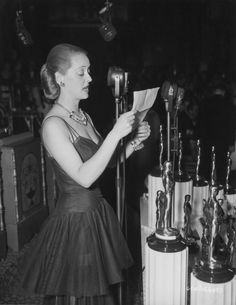 Bette Davis reads a letter of thanks from the Motion Picture Academy to President Franklin Delano Roosevelt at the Academy Awards dinner, February 1941