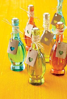 Colored-glass bottles of jalapeño-infused olive oil are embellished with raffia and crafty tags. #shopfesta