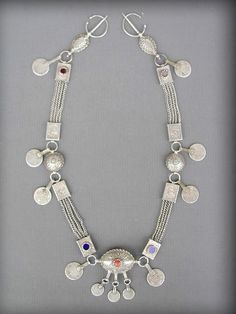 Very rare antique Berber silver jewellery set from Rif region, in North Morocco, Nador or Kenifra.   Consisting of a pair of Fibulae, moulded and chased, connected with a silver chain, small chased boxes and and a small hollow ornament ( Fekroun ). Decorated with a red coral beads and antique arabic silver coins.  The coins are dated from 1312 to 1331 from Hegira ( 1894 to 1913 AD ) Certainly made by a master jewish silversmith, ca early to mid 1900s.