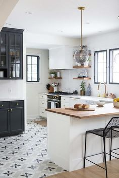 Black and white themed kitchen boasts stunning star tiles from the Cement Tile Shop accented by black side board cabinets, with china cabinets on the top and a quartz countertop from Cambria Ella sat atop the lower half, painted in Wrought Iron by Benjamin Moore.