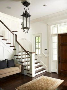 Showy Stairs  Here's a first impression: The front hall graciously welcomes with an architecturally point-on gas lantern, divided sidelights, and crisp white wainscoting. Stairs become an attention-grabbing centerpiece by mixing wood and white paint. Recessed panel newel posts echo the exterior columns.  LUXURY TOUCH: Hardwood floors throughout the home are made from black walnut.