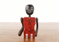 A vintage black dancing man or limberjack wooden toy, with a red zoot suit, but missing his legs.