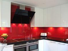 White kitchen with red glass splash backs.