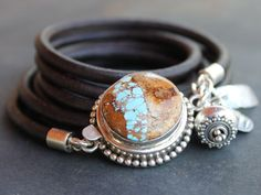 ALONG THE PATH of Self Discovery Turquoise and sterling silver leather wrap bracelet with sterling silver charms. Take inspiration from the extraordinary stone of this bracelet with a river of turquoise running through earthy brown. A reminder that lifes journey is always uncovering new vistas and growth moments. A trio of sterling silver charms dangle to one side, a rock cairn charm, a rustic hammered bridge bar and a graceful granulated silver lantern bead, momentos of milestones along the…