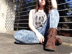 Gray sleeveless graphic t, acid wash jeans, and combat boots.