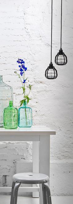 Colored glass jars on white brick =Love