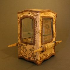 This wooden sedan chair, with curved cardboard top and back, has three bevel-edged windows, opening door with brass working handle, glass shelved interior, and is covered both inside and outside with rich silk and velvet brocade fabrics and gilt metallic borders.