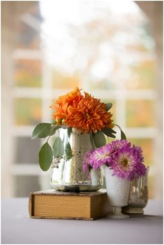 orange and purple wedding flowers in small vases with books // Photo by Ellen Leroy