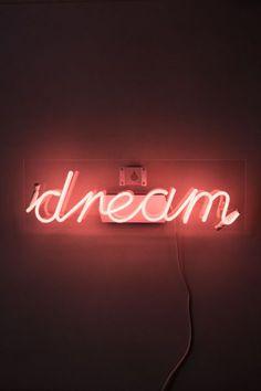 """O letreiro de Neon """"dream"""" é um charme, e fica maravilhoso no quarto, na sala, ou em qualquer lugar da casa! Ele vem fixo em uma chapa de acrílico que você pendura na parede como um quadro, e liga na tomada!"""