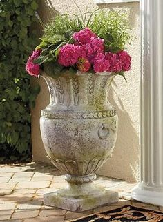 Flank your front door to make a bold statement at your entryway with your Apian Vessel Outdoor Planter; a statuesque planter adorned with elegant leaf, garland and petal displays.