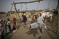 A boy and his sister enjoyed a ride on a swing in the outskirts of Islamabad, Pakistan, Thursday. (Muhammed Muheisen/Associated Press)