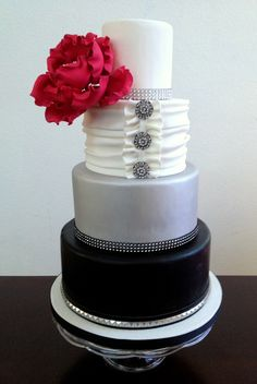 - Fondant wedding cake. Bottom tier is airbrushed black with a faux leather and studded band. Third tier is airbrushed silver. Second tier is decorated with horizontal fondant swags using 1/2 satin ice fondant and 1/2 satin ice gumpaste. Brooches are sewology buttons from Hobby Lobby. Red peony flower from CalJava.