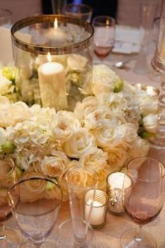 low centerpieces with candles, hurricanes and flower wreaths by raquel
