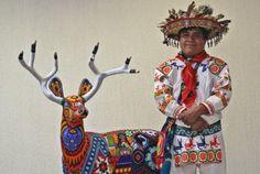 """Los Huicholes usan una camisa y pantalón bordados con punto de cruz, un cinturón de lana tejido, llamado """"peyotera"""", tres morrales, collar, pulsera y pectoral de chaquira, decorada un águila bicéfala, un estandarte de """"Ojo de Dios"""" y sombrero de plumas."""
