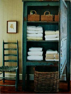 Bringing blue into the bathroom with an antique cupboard for towels.