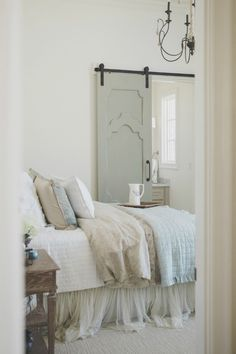 French country farmhouse pale blue and white bedroom with Duck Egg blue barn door. Sherwin Williams Alabaster paint color on walls. Brit Jones Design. Discover inspiring understated neutrals to try in your own home.