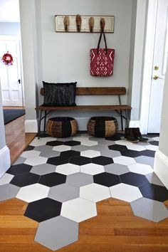 Hex tile mudroom with transition to wood floor kitchen. Loving the Ann Sacks tiles and CB2 bench.