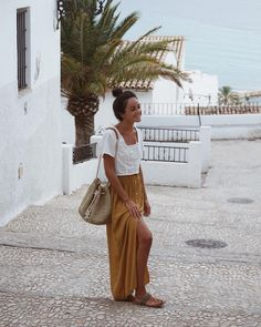 Goldenrod skirt, white embroidered top, woven bag