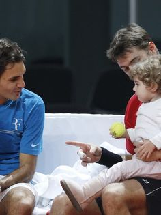 Such a cute picture of Stan Wawrinka and his daughter, Alexia, at Davis Cup practice. Looks like he's introducing her to Roger Federer!