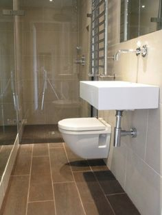 Long Narrow Bathroom Design Ideas - floating toilet, frameless glass shower door & mirrors on both walls make room look wider & more open