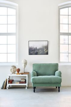 Green is our latest colour obsession | Green Howard style armchair | huge industrial style windows | sideboard with figures and busts | IKEA Stocksund armchair with a Bemz cover in Thyme Brera Lino by Designers Guild