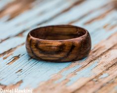 A unique solid wood ring for the whiskey drinker in your life!  This is a hand-turned oak wood ring cut from used Jack Daniels whiskey barrels, custom made to your specifications - choose the size, width, and shape from the options to create your own handmade ring!  Your ring will have a similar lo