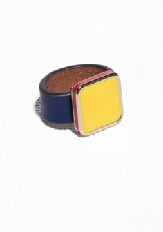 Vivid colour blocking with a gilded finish creates a fresh mix of sporty elegance in this angular leather and brass ring.
