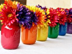 What a beautiful way to add color to anything with these painted mason jars that double as vases! Painted Mason Jar Centerpiece | DIY Craft Tutorial Fiesta Centerpieces, Rainbow Wedding Centerpieces, 60th Birthday Centerpieces, School Centerpieces, Mason Jar Centerpieces, Mexican Centerpiece, Rainbow Centerpiece, Colorful Centerpieces, Paint For Mason Jars