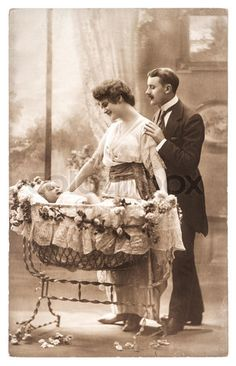 Antique photo of father, mother and infant / baby in a regal bassinet / rocker, Paris, France circa 1920.