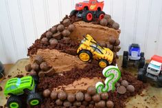 A monster truck cake covered in chocolate candies and figured from blaze and the monster machines on an old cookie sheet with a white background