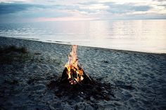 Camp fire on beach with still water and twilight