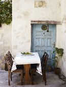 door, colors, stone house, table/chairs/table clothe, plant to side