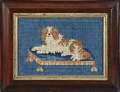 """British Needlepoint Panel of a Spaniel, second quarter 19th century, the canine modeled reclining on his dog bed, verso affixed with a label, printed """"Worked in 1838 by William Kitchen, aged 8 years"""", sight 11-3/4"""" x 5"""". Glazed and presented in a mahogany-veneered frame with a giltwood liner."""