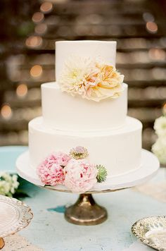 White wedding cake on a vintage stand topped with fresh blooms. Destination Wedding in Hawaii, Pink, Butterflies || Colin Cowie Weddings