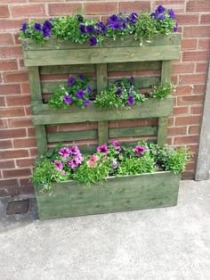Pallet turned on its end with the blocks used as fixing points for slats from another pallet screwed to them to form the planting troughs on the top and middle sections. The larger, deeper trough at the bottom is approx. 12 inches deep again formed from using slats from another pallet. Clear polythe…
