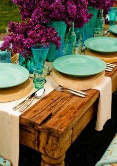 Des couleurs fortes et une déco champêtre et raffinée : table rustique et bois, tissu naturel, vaisselle et verres vert d'eau et fleurs violettes.