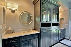 This master bathroom has black cabinets that give this space plenty of storage. The neutral countertops are a nice contrast to the dark vanity.