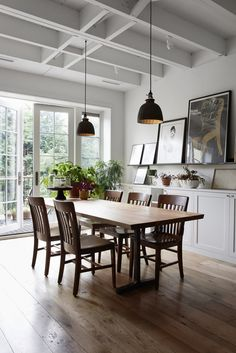 "A mix of old wooden office chairs surround a mango wood table assembled at From the Source. The gilded glass pendant lights came from an antiques store on Atlantic Avenue: ""They're nice because they cast a golden light."" The couple bought the white porcelain cabinet knobs on eBay."