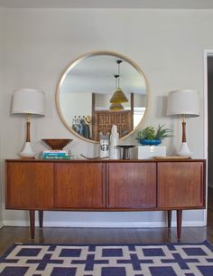 Love the contrast and pairing of this circular mirror and long Mid Century credenza