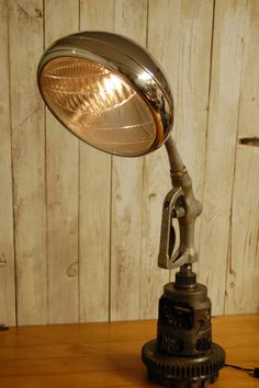 Desk lamp made from a 32 ford head light, old gas pump handle, and transmission parts.